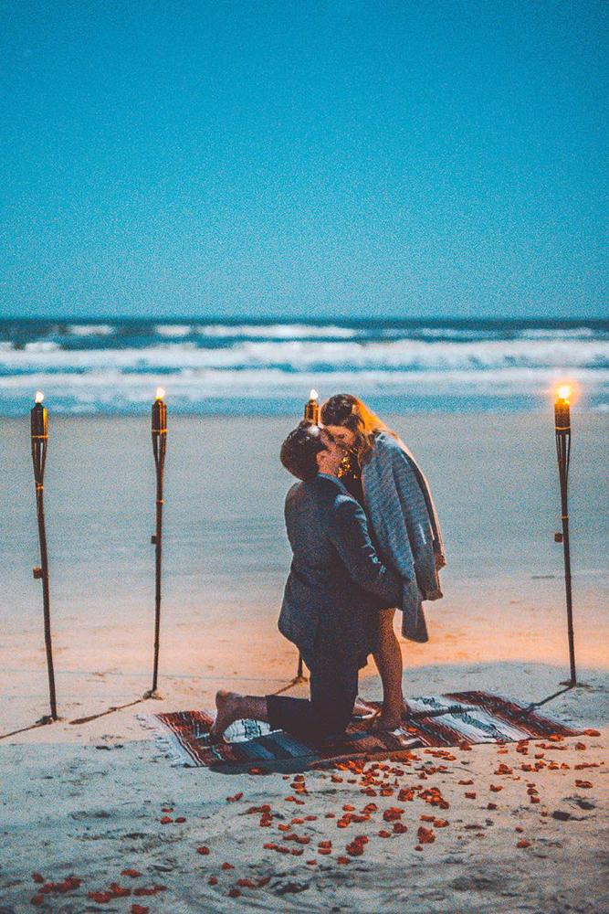 beach proposals kissing in a torch decoration