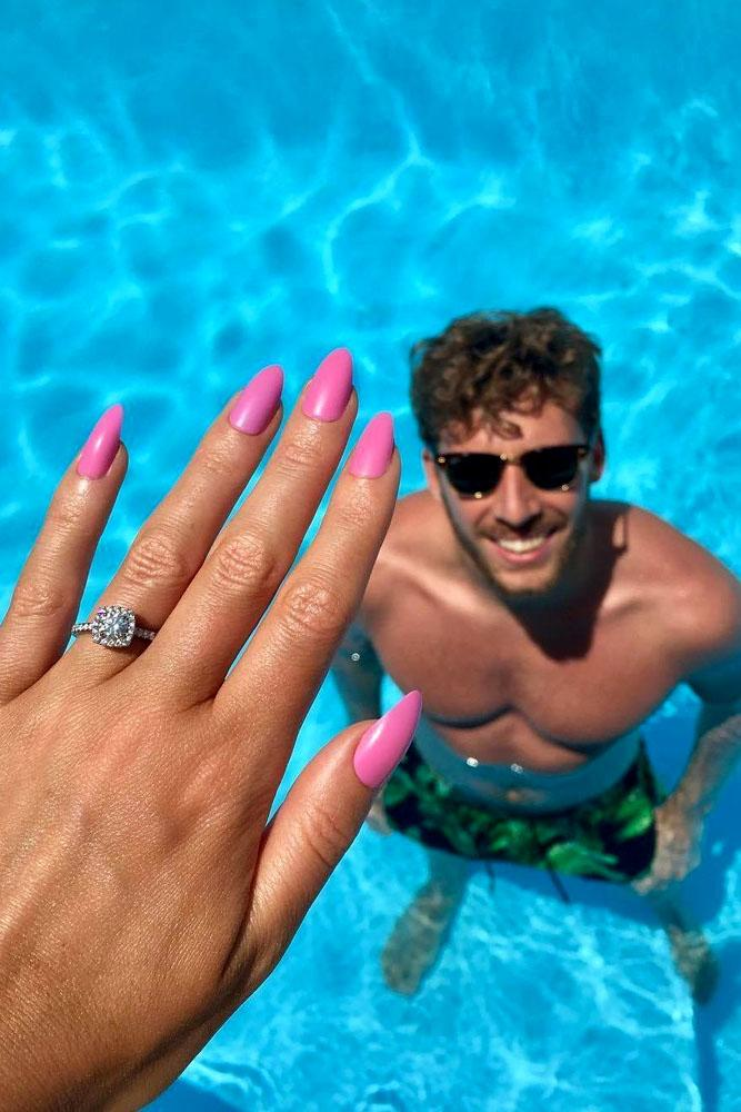 summer proposal ideas man in water and her hand with engagement ring