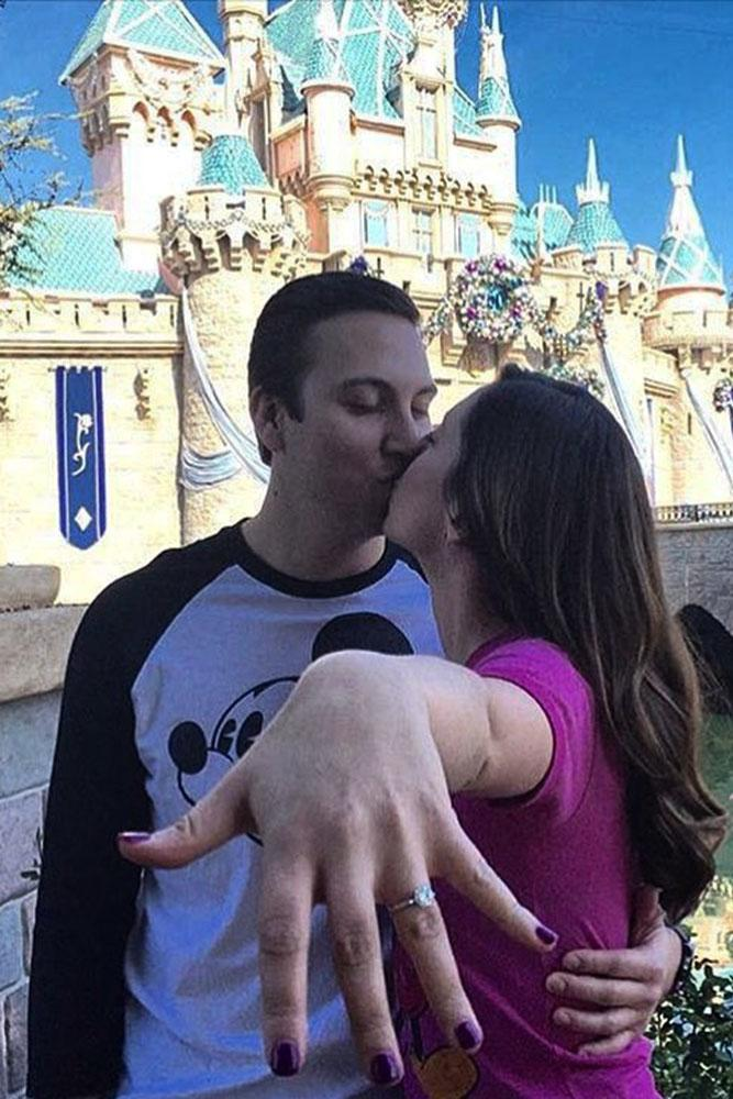 Disney proposals kiss on disney castle backgraund and engagement ring on her finger