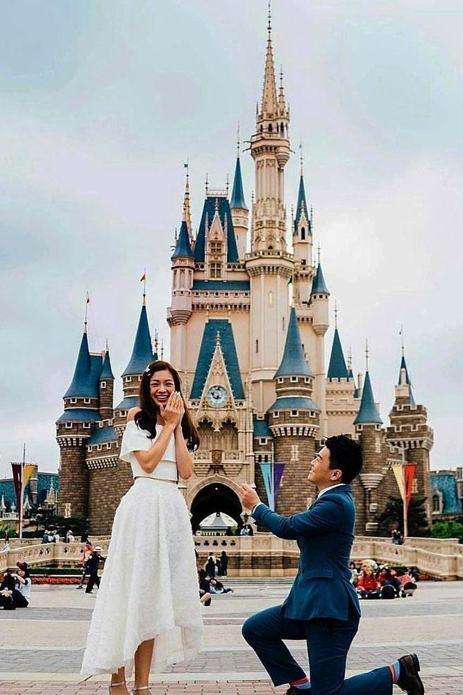 Disney proposals man is on one knee on castle background