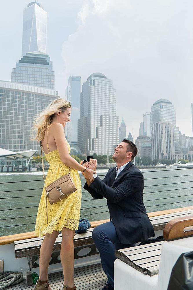 engagement photo ideas man propose a woman boat city view