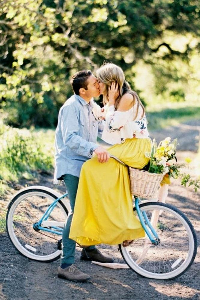 engagement photo ideas woman sits on bike man kisses her