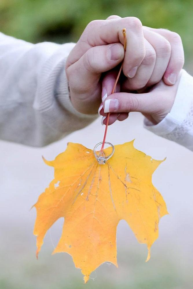 fall proposal ideas two hands with yellow leave and engagement ring idea