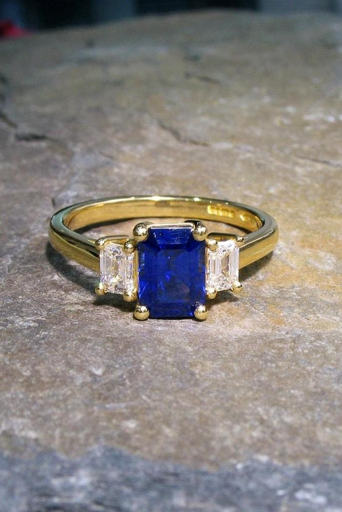 three stones engagement rings yellow gold step cut sapphire with emerald cut shoulder diamonds
