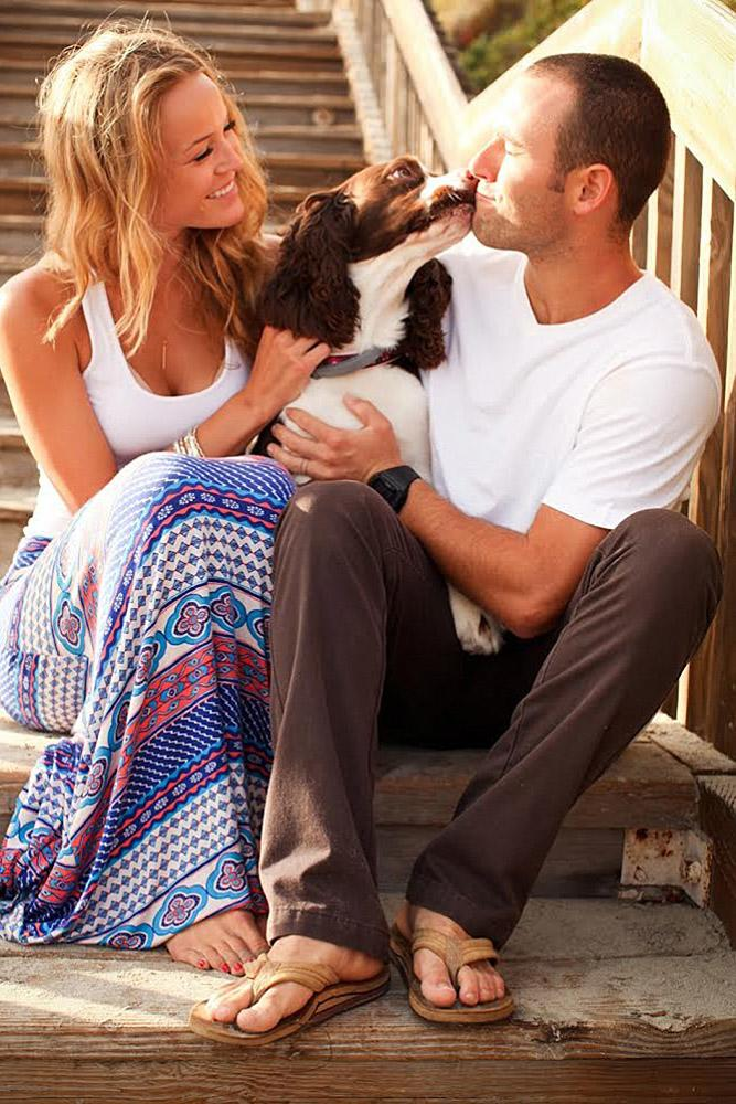 engagement pictures with pets dog kisses a man the girl is smiling