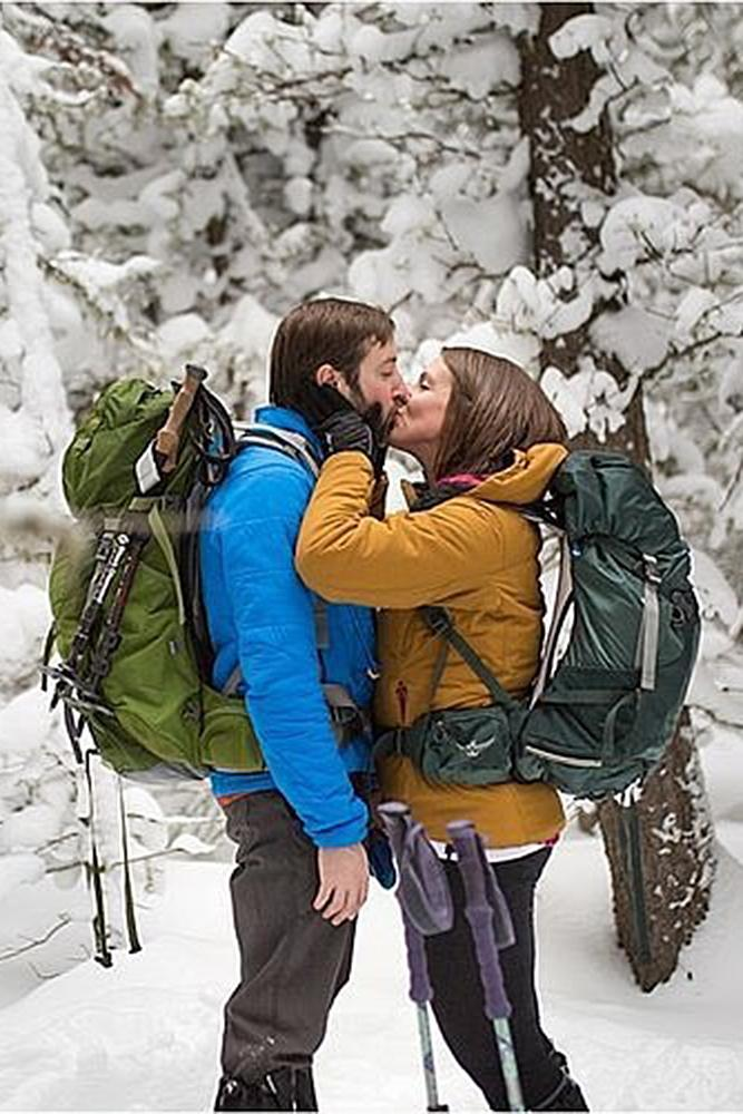 winter engagement photos skis man and woman kiss engage