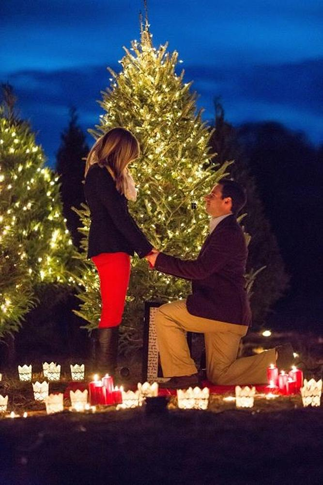christmas proposal man propose woman near tree