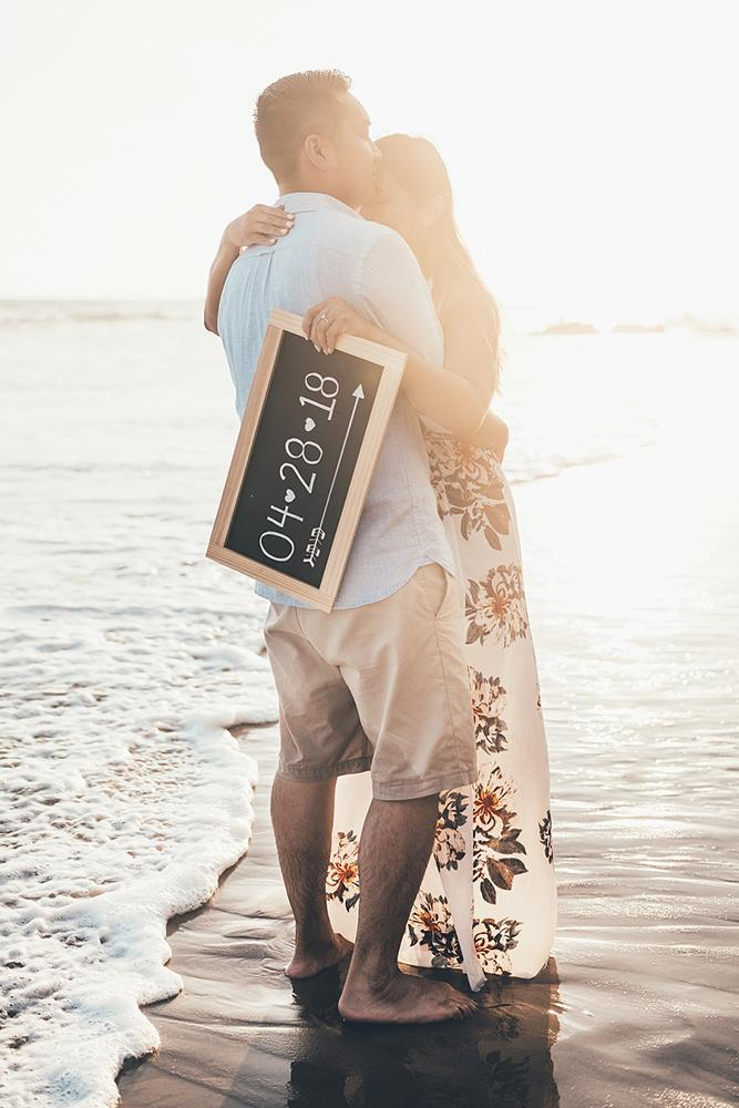save the proposal date woman is hugging a man near tidal sea holding a blackboard