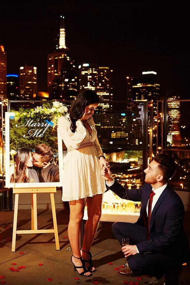 perfect proposals inspired night time roof proposals with candles and flowers